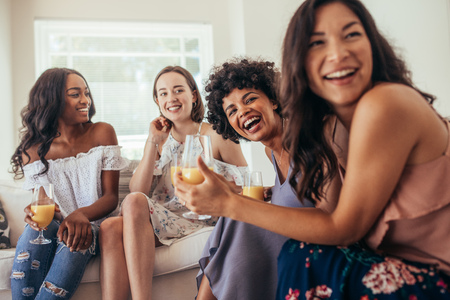 Diverse group of female friends enjoying at a party and laughing. Women friends having a party at home and looking away. Banque d'images