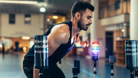 Fit young man doing hand eye reaction training with lights sensors in sports lab. Male athlete optimizing the balance, motor skills and vision by lights in gym. Stock Photo