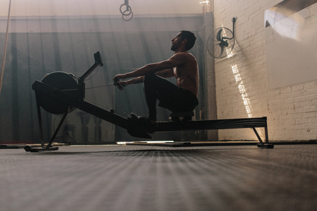 Muscular male using rowing machine in gym. Fit man doing workout in fitness club.