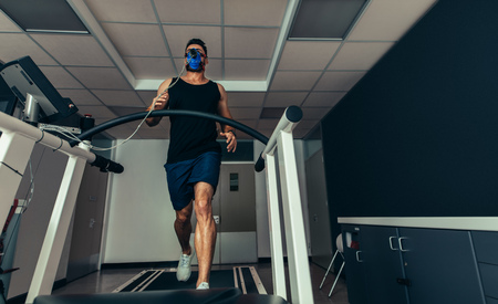 Male athlete with mask running on treadmill to analyze his fitness performance. Runner testing his performance in sports science lab. Stock Photo