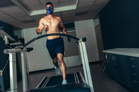 スポーツラボで彼のフィットネスを調べる男性アスリート。トレッドミルでパフォーマンステストを行うマスク付きランナー。 写真素材