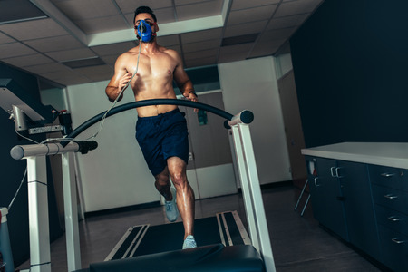 Male athlete examining his fitness in sports lab. Runner with mask doing a performance test on treadmill. Banco de Imagens