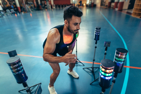 Sportsman exercising with lights around to improve reaction time at gym. Athlete using a visual stimulus system at sports lab.