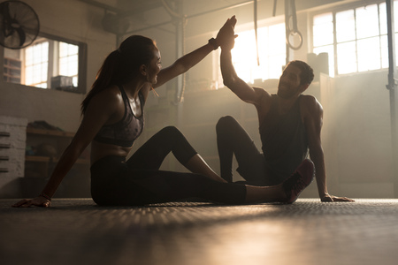 Healthy man and woman sitting on floor and giving each other high five at the gym. Fitness people after successful exercising session in gym.