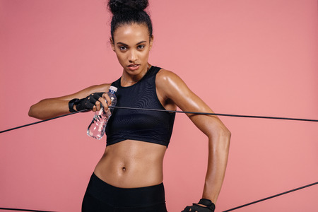 Strong woman exercising with elastic band. Female athlete doing workout with resistance band.