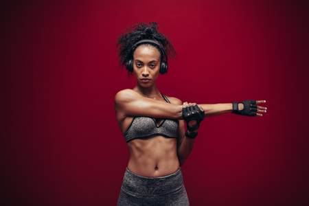 Fit young woman in sportswear and headphones stretching her arms. Portrait of african woman doing warm up exercises against red background.