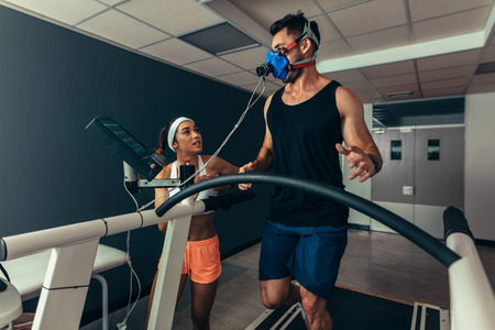Woman giving instruction to male runner on treadmill in laboratory. Runner with mask on treadmill in laboratory with woman trainer. Banco de Imagens