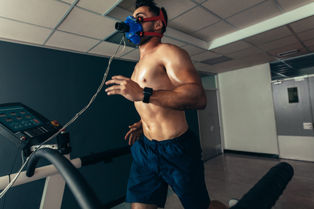 Athlete doing a performance test in sports lab. Runner with mask running on treadmill machine and testing performance.
