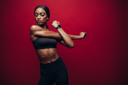 Healthy black woman wearing fitness outfit on red background and stretching her arms. African female doing stretching exercise. Stockfoto