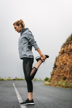 Fitness woman doing stretching exercises on an empty road. Woman in sweatshirt stretching her leg.
