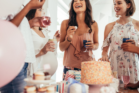 Group of women at a baby shower enjoying food and drink. Pregnant woman celebrating baby shower with female friends at home. Фото со стока