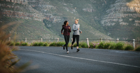 Two women going for an early morning run. Fitness runners in track suits running on road.