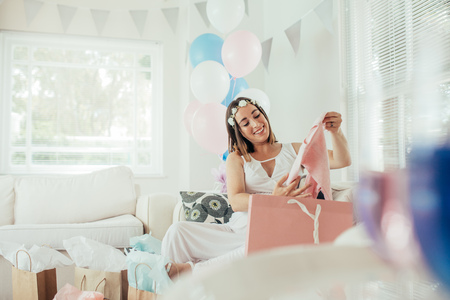 Expecting mother pulls out new clothing for baby at shower. Female opening presents received at baby shower party.