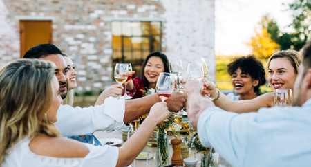 Group of men and women toasting wine at outdoor party. People having drinks during lunch at garden restaurant.