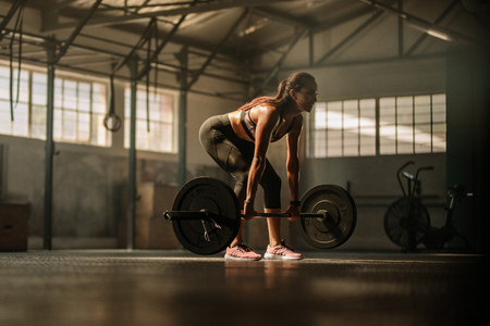 Fit young female athlete lifting heavy weights. Fitness model performing weight lifting exercise at gym. Stock Photo