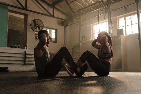Fitness couple doing sit ups together in health club. People doing abs workout in gym.