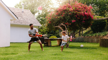 Man playing with little boy in backyard lawn. Father and son playing with water guns outdoors. Stockfoto