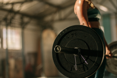 Woman exercising with heavy weights in health club. Focus on heavy weight barbell in hands of female athlete.
