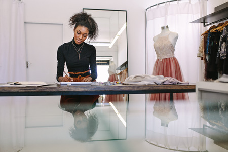 Female fashion designer sketching a design sitting at her table. Fashion entrepreneur engrossed in making a drawing at her desk in her cloth shop. Foto de archivo - 95439959