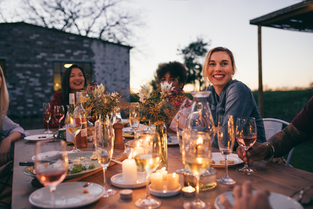 Group of friends enjoying outdoor party in garden restaurant . Millennials enjoying dinner outdoors