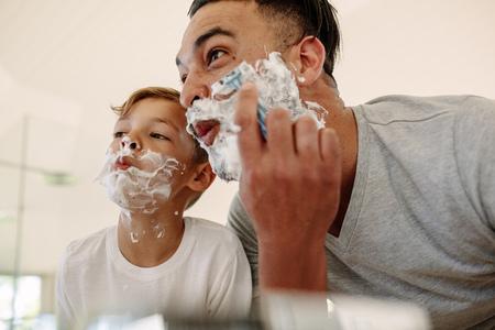 Padre e figlio che fanno i fronti divertenti mentre si radono nel bagno. Giovane e ragazzino con schiuma da barba sui loro volti si radono e si guardano allo specchio.