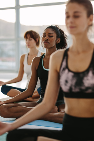 Fitness people practicing mindfulness and peaceful yoga meditation workout. Group of women meditating in lotus pose at fitness studio.