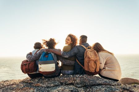 Group of young men and women sitting on mountain top and admiring sunset. Young woman with friends enjoying a day outdoors. Stock Photo