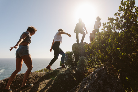 Group of friends on a mountain. Young people on mountain hike on a summer day. Men and women climbing rocks. Banque d'images - 95742325