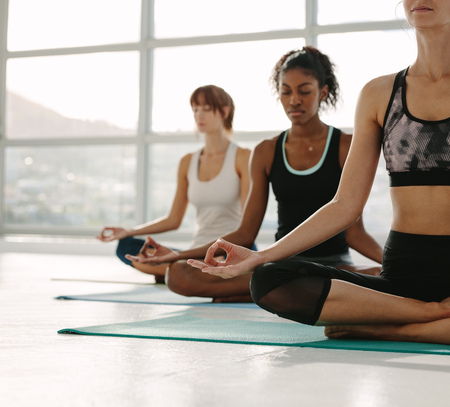 Women meditating while sitting in fitness studio. Young woman practicing yoga in gym class with females sitting around.