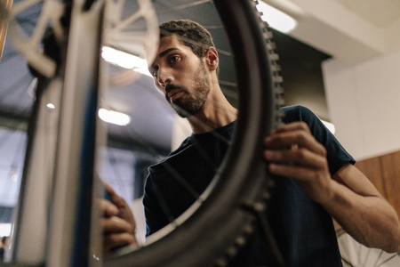 Worker aligning a bicycle wheel in workshop. Man working on a bicycle in a repair shop.