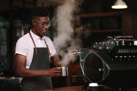 Coffee shop owner preparing coffee on steam espresso coffee machine. Man working in his coffee shop wearing an apron. Standard-Bild - 96073693