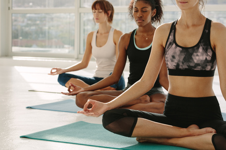 Three women in yoga class sitting on fitness mat with legs crossed and hands on knees. Female meditating in lotus pose at fitness studio.