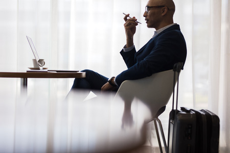 Businessman speaking on mobile phone while sitting at table in waiting lounge at airport. Male business traveler sitting at cafe inside airport with smart phone.