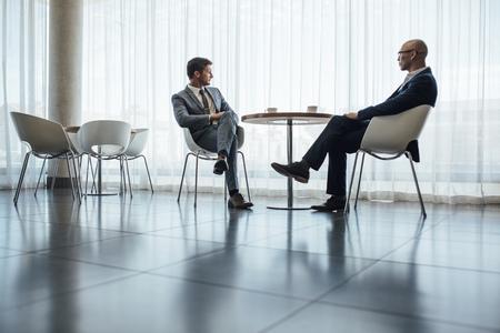 Twee mensen bijeen in kantoor café. Zakelijke partners zitten aan café tafel in moderne kantoor.