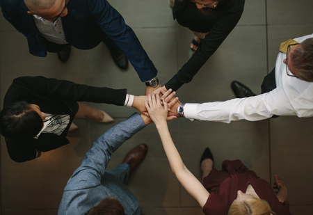 Business team putting hands together at the office. Top view of diverse business people joining hands for unity and teamwork.