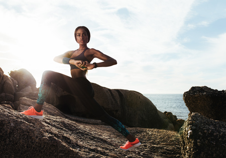 Fit young female runner doing stretches. Young woman stretching outdoors on rocks at beach.