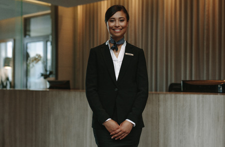 Happy smiling female receptionist in hotel. Beautiful concierge in uniform waiting for welcoming the guests. Foto de archivo