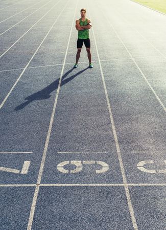 Runner standing on running track with hands folded. Athlete wearing earphones with mobile phone fixed in arm band. Reklamní fotografie