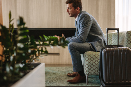 Man in suit sitting at airport business lounger with his luggage. Business traveler waiting for this flight.