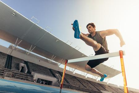 陸上競技中にハードルを飛び越えるランナーをクローズアップ。スタジアムでハードルレースを走るアスリート。