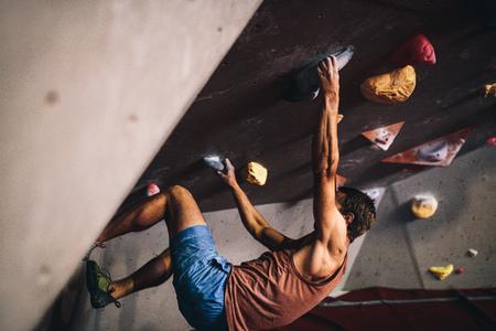 Athletic man bouldering at an indoor climbing centre. Professional climber climbing wall upside down at an indoor climbing gym.