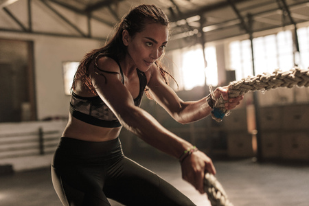 Fitness woman using battle ropes for exercising. Female working out with battle ropes at cross gym.