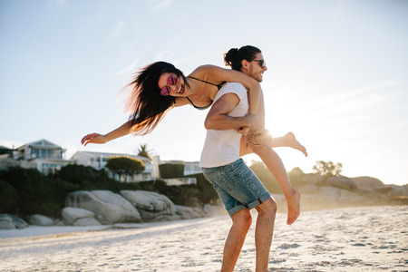 Happy young man carrying his woman on the beach. Couple enjoying a day at the beach. 版權商用圖片 - 96535283