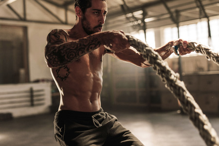 Strong and muscular man using training ropes for exercise at gym. Athlete working out with battle ropes at gym.