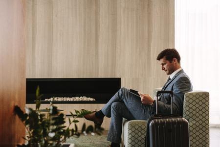 Vista lateral del ejecutivo de negocios leyendo una revista mientras espera su vuelo en el salón del aeropuerto. Hombre en el área de espera del aeropuerto leyendo una revista.