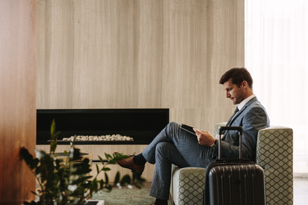 Side view of business executive reading a magazine while waiting for his flight at airport lounge. Man at airport waiting area reading a magazine. Stockfoto