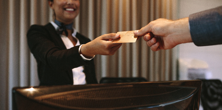 Close up of businessman paying with credit card at reception desk in hotel. Business man giving credit card to hotel receptionist for payment of his room. Focus on hands. 版權商用圖片