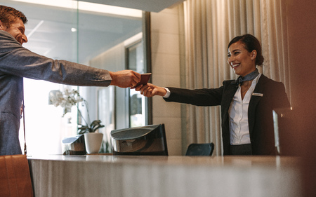 Businessman passes his passport to a smiling receptionist behind the hotel counter. Check-in process in luxurious hotel. Zdjęcie Seryjne