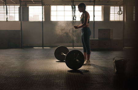 Strong young woman about to lift heavy weights at gym. Fitness female doing workout. Stockfoto