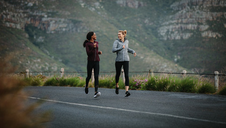 Women running on road early in the morning with hills in the background. Fitness women jogging on road.